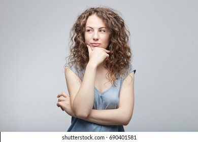 Portrait of beautiful casually dressed young Caucasian woman having doubtful expression, looking away cunningly in indecisiveness, holding her chin,trying to find best solution. Body language concept.
