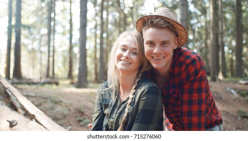 Portrait of beautiful caucasian couple spending time in a forest during sunny day. Smiling friends looking at camera in the woods.