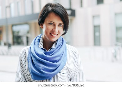 A portrait of beautiful caucasian female with short dark hairs wearing striped shirt and light blue scarf and smiling at the camera while standing on a blurred urban background.