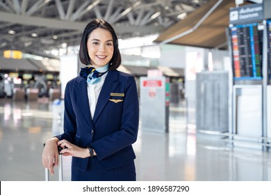 Portrait of beautiful Caucasian flight attendant staff smiling and looking at camera with confidence face and happiness in airport terminal. Feeling welcome all customer or passenger to the airplane.