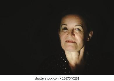 Portrait of a beautiful Caucasian mature woman in 60s in a dark room.