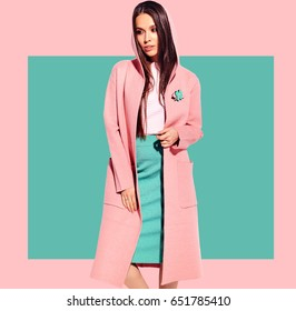 Portrait of beautiful caucasian smiling brunette woman model in bright overcoat and summer stylish skirt posing  on pink and blue background