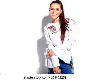 Portrait of beautiful caucasian smiling brunette woman model in white blouse and summer stylish blue jeans with flowers print isolated on white background