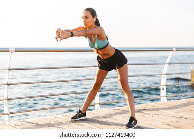 Portrait of beautiful caucasian sportswoman 20s in tracksuit bending forward and stretching arms in sunny morning with sea background