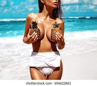 portrait of beautiful caucasian sunbathed woman model with dark long in swimsuit posing on summer beach with white sand on blue sky and ocean background. Covering  her big brest with small pineapples