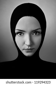 Portrait of beautiful caucasian woman in black tissue posing on grey background