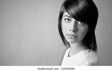 Portrait of beautiful caucasian woman with beautiful dark hair posing on grey background
