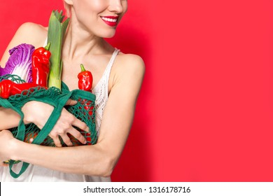 Portrait of beautiful caucasian woman holding grocery bag. Healthy lifestyle concept, vegetables, diet