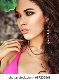 portrait of beautiful caucasian  woman model with dark long hair in pink swimsuit posing on near green tropical leaf