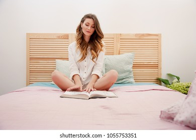 Portrait Beautiful Caucasian Woman reading a book sitting in lotus pose on a bed