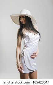 Portrait of beautiful Caucasian woman wearing short white dress and large white hat