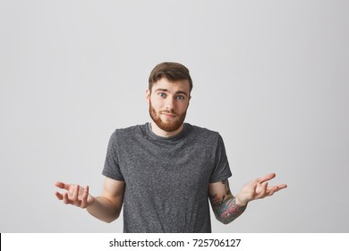 Portrait of beautiful caucasian young bearded man with trendy hair and tattoo on left arm looking in camera with confused emotion, spreading hands. Guy don't know what to answer his girlfriend.