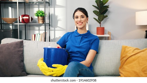 Portrait of beautiful Caucasian young female in yellow gloves holding bucket with cleaning sprays and tools sitting on sofa after cleaning home and smiling to camera domestic work housekeeping concept