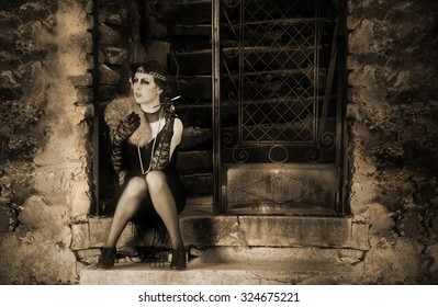 Portrait of The Beautiful  Charleston Retro Woman in Black Lace and Accessories in Style 1920 - 1930 Sitting in the Old Metal Gate