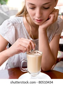 portrait of beautiful charming woman is stirring coffee in outdoor cafe and thinking