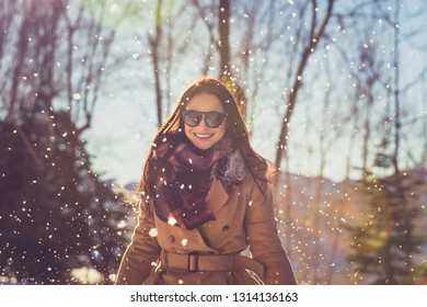 Portrait of a beautiful cheerful female enjoying winter snowfall in the park, with pleasure spending wintertime holidays outdoors