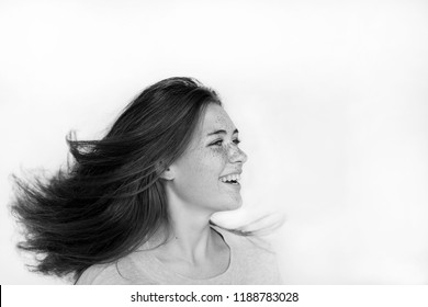 portrait of a beautiful cheerful girl with freckles on her face and a charming smile, dancing and whirling, with long flowing hair. people, lifestyle, sport, dance, happiness concept
