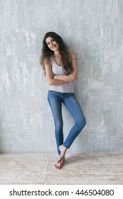 Portrait of beautiful cheerful girl with long brunette hair posing barefoot on wooden floor and cement gray wall