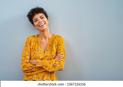 Portrait of beautiful cheerful girl smiling and looking at camera. Happy african woman in casual on blue background. Brazilian stylish woman with crossed arms and curly hair isolated with copy space.