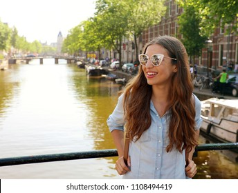 Portrait of beautiful cheerful girl with sunglasses looking to the side on one of typical Amsterdam channels, Netherlands, Europe