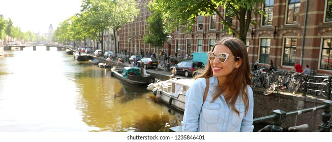 0b5dcf9047b96 Portrait of beautiful cheerful girl with sunglasses looking to the side on  one of typical Amsterdam