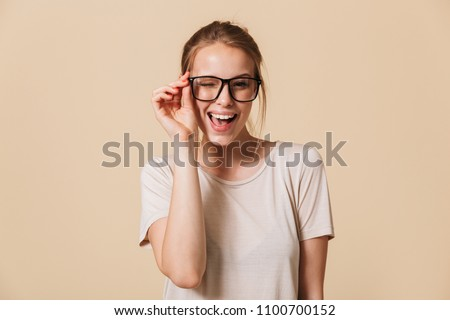 2ead2a6a2ee9 Portrait of beautiful cheerful woman 20s wearing basic t-shirt touching  eyeglasses and smiling at