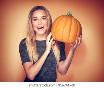 Portrait of beautiful cheerful woman with pumpkin over orange background, celebrating happy Thanksgiving day