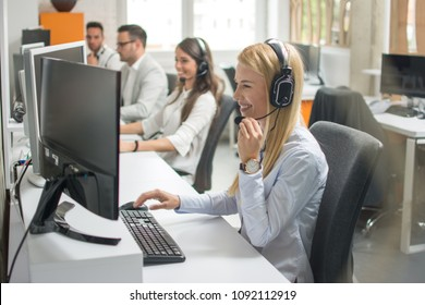 Portrait of beautiful and cheerful young woman telephone operator with headset working on desktop computer in row in customer service call support helpline business center