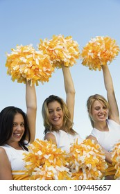 Portrait of beautiful cheerleaders cheering against sky