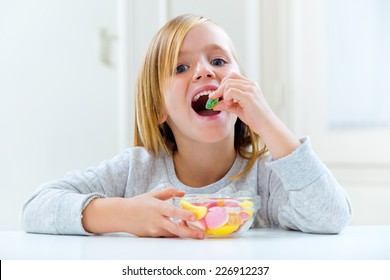 Portrait of beautiful child eating sweets at home.