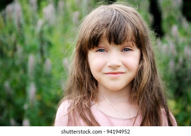 Portrait of beautiful child girl with long hair outdoors