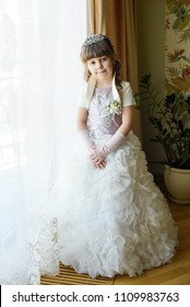 Portrait of the beautiful child little girl bride against a window indoors