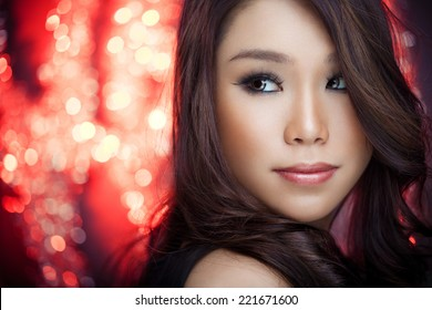 Portrait of a beautiful Chinese woman looking over a shoulder in front of defocused red decorative lights (can be used for a Chinese New Year, New Year, Christmas... concept)