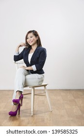 Portrait of a beautiful Chinese woman posing with a chair.