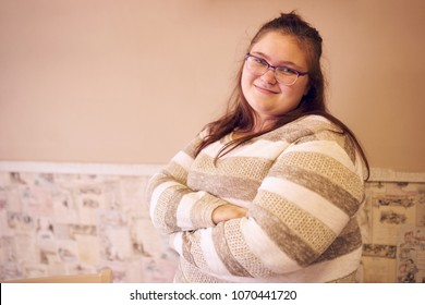 Portrait of beautiful chubby caucasian woman standing in front of a two toned wall with decorated wall paper and her arms crossed while looking at camera and smiling.
