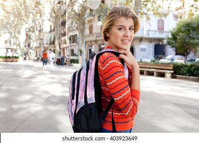 Portrait of beautiful college student in a city avenue with trees and stone pavement, carrying a backpack, turning and smiling at camera, outdoors. Student lifestyle, sunny street exterior.