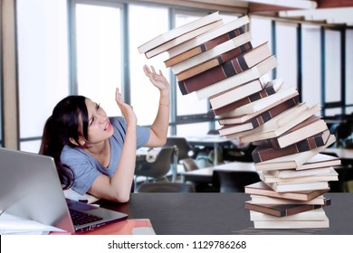 Portrait of a beautiful college student holds falling books while studying and sitting in the classroom
