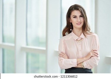 Portrait of beautiful confident businesswoman standing with her arms folded