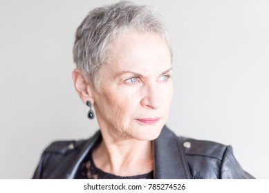 Portrait of beautiful contemporary older woman with short grey hair and blue eyes against neutral background (selective focus)