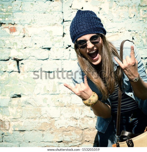 89574f447871 portrait of beautiful cool girl gesturing in hat and sunglasses over grunge  wall