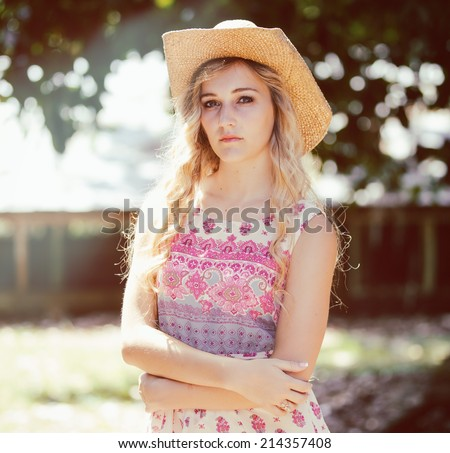 26acfa18ed4 Portrait of a beautiful country girl with curly blonde hair standing in the  sun wearing a cowboy hat and a sundress. - Image