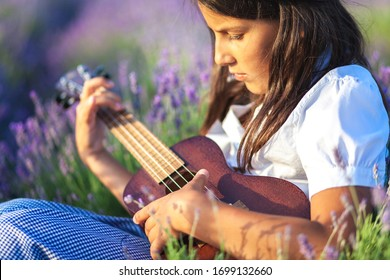 Portrait of a beautiful country girl who plays on the ukulele among lavender flowers