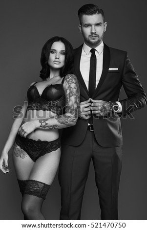 559e66798f Portrait of a beautiful couple  brutal man in elegant suit and sexy girl  with a tattoo in lingerie on gray background - Image