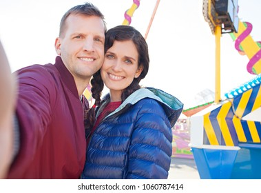 Portrait of beautiful couple with heads together looking smiling, colorful amusement park rides, taking selfies networking outdoors. People using technology in funfair, leisure recreation lifestyle.