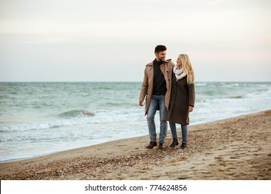 Portrait of a beautiful couple in love hugging while walking along the beach