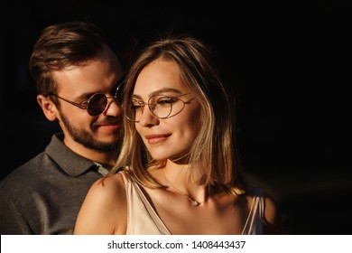 Portrait of beautiful couple in love. Man and woman in sun glasses posing on sun. Girl and her boyfriend in sunglasses on black background