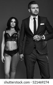 Portrait of a beautiful couple: man in elegant suit and sexy girl with a tattoo in lingerie on gray background