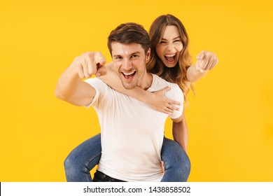 Portrait of beautiful couple man and woman in basic t-shirts pointing finger at camera together while doing piggyback ride isolated over yellow background