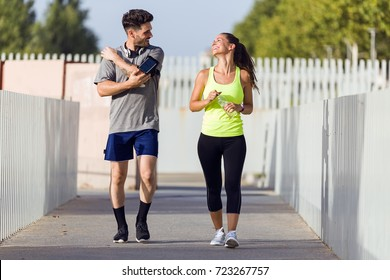 Portrait of beautiful couple running in the street.