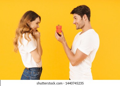 Portrait of beautiful couple standing together while handsome man making proposal to happy woman with ring box isolated over yellow background